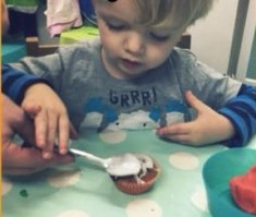 BEN ENJOYS LEARNING HOW TO SPREAD ICING WITH A SPOON!